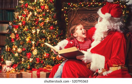 happy child girl hugging Santa reading book and laughs