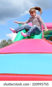 Happy child girl jumps on the inflatable playground
