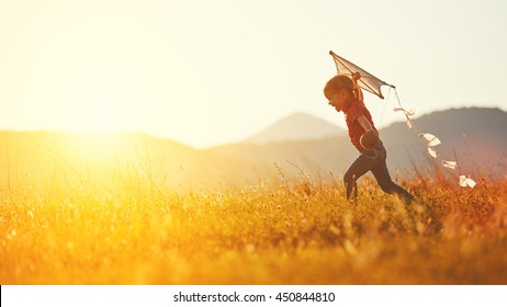 Photo of happy child girl with a kite running on meadow in summer in nature
