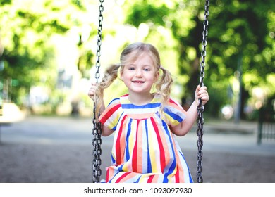 Happy child girl laughing and swinging on a swing at the play ground in summer.