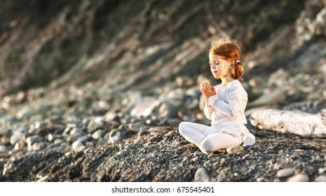 Happy child girl meditates in lotus position, engaged in summer yoga outdoors