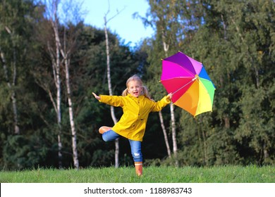 Happy child girl with a multicolored umbrella and rubber boots an autumn walk.