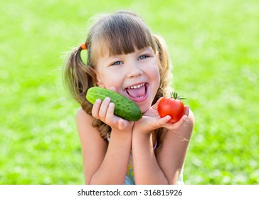 happy child girl on grass loan with healthy vegetables in her hands