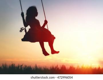 Happy child girl on swing in sunset summer