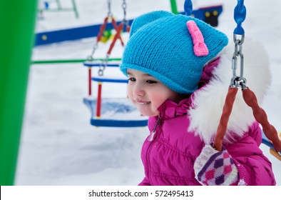 Happy child girl on swing in sunset winter. Little kid playing on a winter walk in nature.