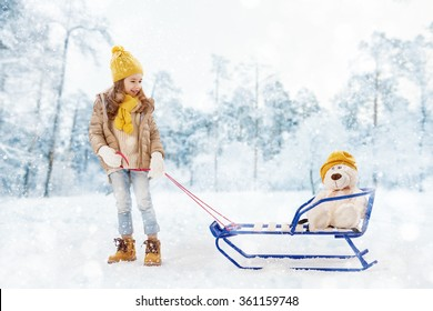 happy child girl plaing with a toy on a snowy winter walk. child rolls a teddy bear on a sled