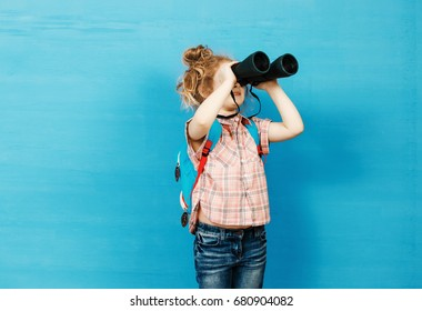 Happy child girl playing with binoculars. explore and adventure