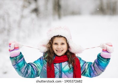 Happy child girl plays with a snow in winter day. Girl enjoys winter, frosty day. Playing with snow on winter holidays. Walk in winter forest.
