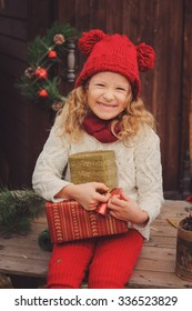 happy child girl in red hat celebrating christmas at cozy wooden country house
