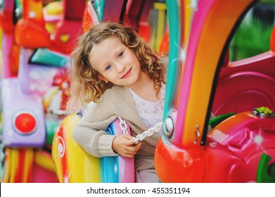 happy child girl riding toy train on funfair on summer vacation