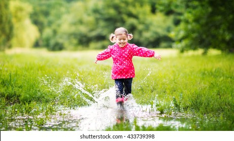 happy child girl running and jumping in puddles after rain in summer