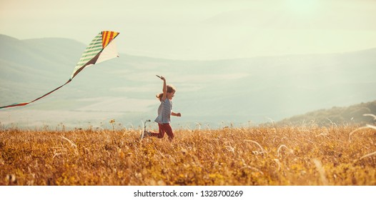 happy child girl running with a kite at sunset outdoors
