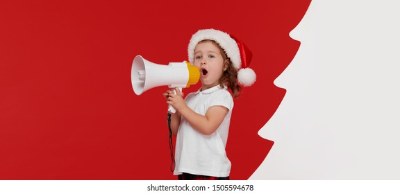 Happy child girl in Santa hat. Kid shouting by megaphone at Christmas decoration. Happy xmas and New Year, winter holiday concept with copy space for text on red background
