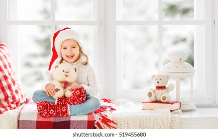 happy child girl sitting in the winter window Christmas