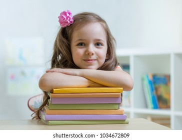 Happy child girl with a stack of books at home