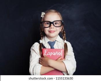 Happy child girl student against spanish language school chalkboard. Learning Spanish concept