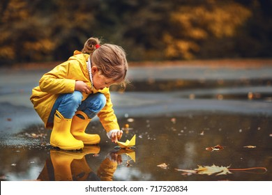 happy child girl with umbrella and paper boat in a puddle in   autumn on nature