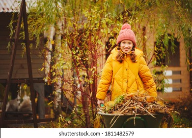 Happy child girl working in autumn garden, helps to remove fall leaves from lawn