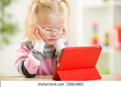 happy child in glasses looking at mini tablet pc screen sitting at table
