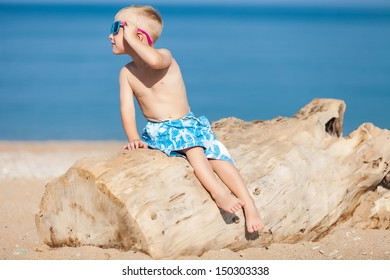 Happy child with glasses sitting on a log at the beach in summer