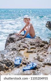 Happy child has a fun on rock beach of mediterranean sea. Holiday summer concept