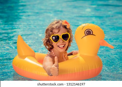 Happy child having fun on summer vacation. Funny kid in swimming pool. Active healthy lifestyle concept