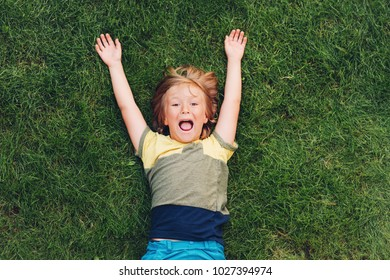 Happy child having fun outdoors. Kid playing in summer park. Little boy lying on green fresh grass, top view