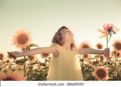Happy child having fun in spring field against blue sky background. Freedom concept