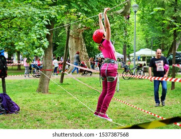 Happy child, healthy teenager girl enjoys rope climbing activity in an adventure park outdoors in Cluj-Napoca, Romania on circa May, 2018.