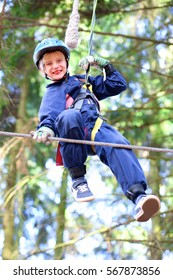 Happy child, healthy teenager school boy enjoying activity in a climbing adventure park on a summer day
