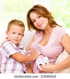 Happy child holding belly of pregnant woman