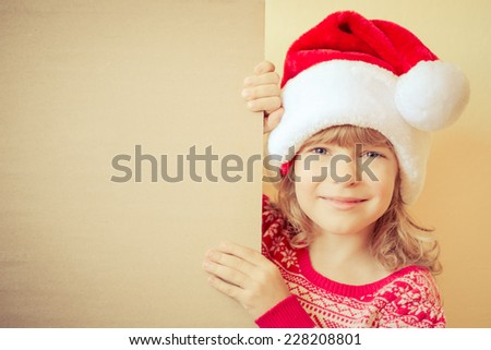655d32859d1 Happy child holding Christmas card blank. Kid dressed in Santa Claus hat  playing at home