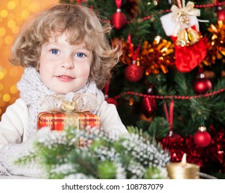 Happy child holding gift against Christmas tree with decorations