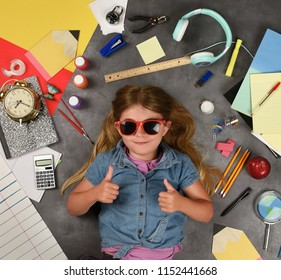 A happy child is holding her thumbs up for a back to school education idea. There are various school supplies around the girl.