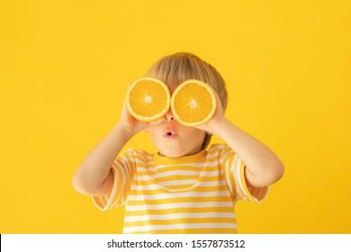 Happy child holding orange. Portrait of funny kid against yellow background