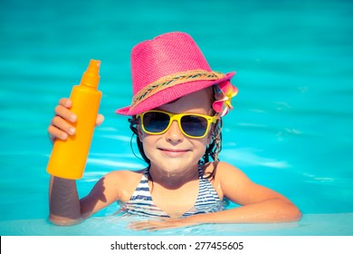 Happy child holding sunscreen lotion in hand. Summer vacations concept