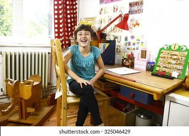 happy child at home sitting on her table in the childrens room