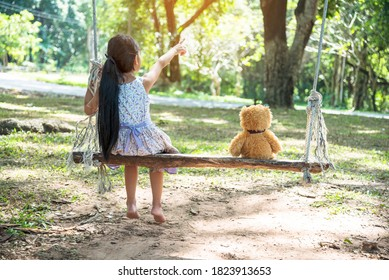 Happy Child hug teddy bear in green park playground. Teddy bear best friend for little kids cute girl. Autism happy funny playing together on playground in happiness family feel love and warm hugs