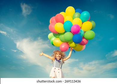Happy child jumping with colorful toy balloons outdoors. Smiling kid having fun in green spring field against blue sky background. Freedom concept