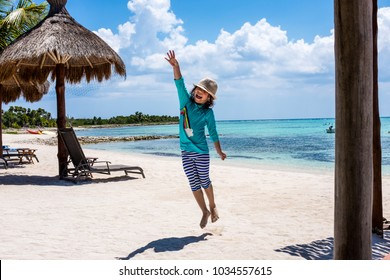 Happy child jumping on a white sand beach with the ocean in the background