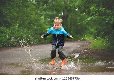 Happy child jumping in puddle in waterproof coat. A boy have fun in rain in a bright raincoat. Kid playing in mud with splash in autumn park. Outdoor fun in the rain weather
