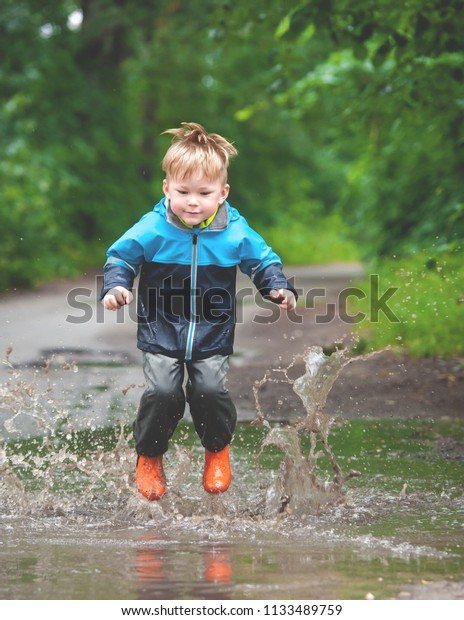 07391fb303809f Happy child jumping in puddle in waterproof coat. A boy have fun in rain in