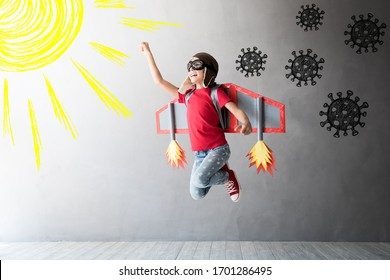 Happy child jumping with toy cardboard wings. Kid pilot flying away from covid virus. Sun and vitamin D concept