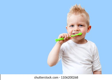 Happy child kid boy brushing teeth on blue background. Health care, dental hygiene, people and beauty concept. Mockup, free space.