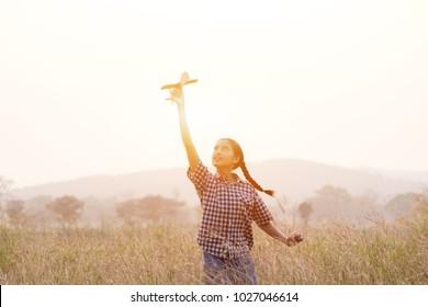 Happy child launching kite on nature at sunset
