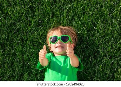 Happy child laying on green grass. Funny kid outdoor in spring garden. Earth day and healthy lifestyle concept