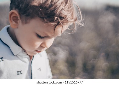 Happy child, little boy looks down, pensive look in a white T-shirt outdoors. Space for Your Text. Retro toned.  Summertime.