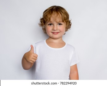 Happy child, little boy showing thumbs up gesture in a white T-shirt isolated on white background. Space for Your Text. Ok sign