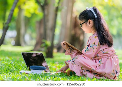 Happy child little girl with glasses reading a books with her laptop at the park.