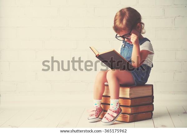 niña feliz con anteojos leyendo libros